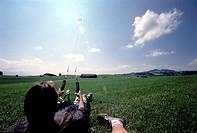 SG F, Freizeit, Hobby, Sport, Drachensteigen, junger Mann mit Lenkdrachen,  drachen steigen im gras liegend festhalten kraft