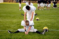 High School Football teams doing pregame stretching exercises