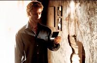 Film, ´Memento´, USA  2001, Regie: Christopher Nolan,  Szene mit Guy Pierce,   mann im halbdunkel, sich polaroid, foto betrachtend, ansehend,