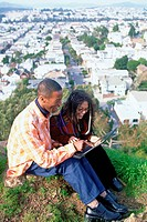 Couple with laptop sitting on hill above city