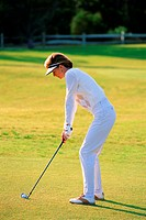 adult female about to hit golf ball on the golf green