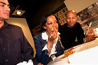 A businesswoman and two businessmen sitting at a table eating Chinese food and working on a project