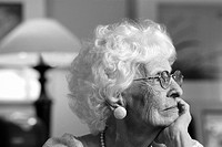 Portrait of a mature adult female with white curly hair wearing glasses