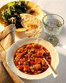 Turkey and bean stew on plates, Mineral water, Bread, Salad