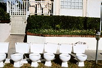 Row of discarded toilets in front of an apartment building