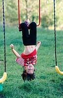 Girl hanging upside down on playset
