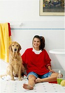 Girl washing her dog in the bathroom