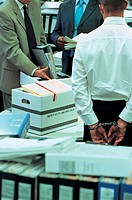 Businessman Standing in An office Wearing Handcuffs and Businessmen Searching Through Folders and Documents