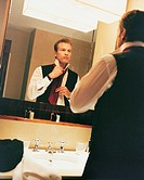 Businessman Fastening His Tie in the Bathroom Mirror of His Hotel Room
