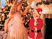 Girl Wearing a Fairy Costume Annoying Her Brother Dressed As Father Christmas