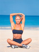Portrait of a Young Woman Sitting Cross Legged on a Beach Doing Stretching Exercises