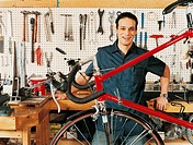 Portrait of a Young Bicycle Mechanic Standing By a Workbench in a Bicycle Shop