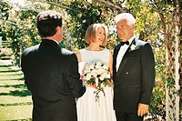 Couple Standing Behind a Priest During a Wedding Ceremony in a Garden