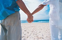Rear View Close up of a Senior Couple Holding Hands on the Beach
