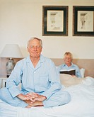 Portrait of a Senior Man Wearing Pyjamas Sitting in the Lotus Position on His Bed in Front of His Wife Reading a Book