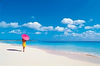 Woman Walking Along a Beach Holding a Parasol
