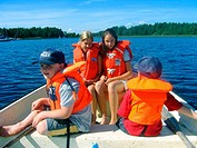 Two 13 year old girls and two brothers, aged 6 and 3, out on a boat on Lake Vättern, all wearing life jackets. Sweden