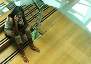 Woman sitting on stairs talking on cell phone, view from above