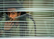 Man looking though blinds