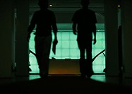 Two people walking through doorway of office, silhouette