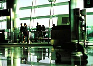 Business people walking through airport terminal gate in the distance