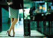 Businesswoman leaning on suitcase with her legs crossed, lower section