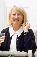 Mature woman with glass of water, smiling after taking medication