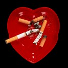 Cigarette butts and ash. Cigarette butts and ash in a heart-shaped ash tray. Tobacco contains the stimulant nicotine which is responsible for the addi...