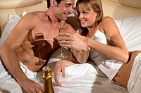 Couple drinking champagne in bed
