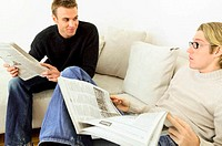 Men reading newspapers on sofa (thumbnail)
