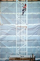 Construction worker climbing up a metal tower