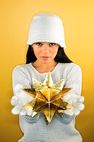 An asian woman wearing a white winter hat, gloves and sweater holds a gold moravian star out to the