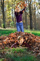A boy lies covered in a pile of leaves as his sister tosses more on him from behind.