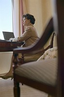 Businesswoman Sitting at Desk, Working on Laptop