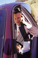 Businessman Sitting in Car While Talking on Cell Phone and Writing in Planner