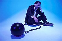 Pondering businessman on ball and chain