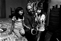 Girl Sitting on Father´s Lap, Playing Saxophone