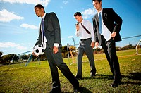 Businessmen on football pitch