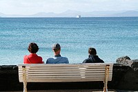 People on bench, watching the ferry from Fuerteventura. Playa Blanca. Lanzarote. Canary Islands. Spain