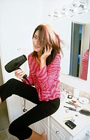 young girl blow drying her hair