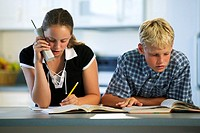 Two teens working on their homework with the boy reads as the girl talks on the phone