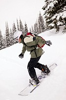 A boy wearing a knapsack snowboards down hill