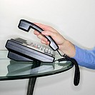Close-up of a businessman´s hand hanging up a telephone
