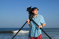 Portrait of a video cameraman standing near the ocean holding his camera and tripod