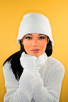 Portrait of an asian woman wearing a white winter hat, gloves and sweater