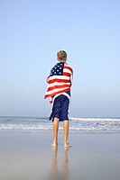 A boy standing at the edge of the ocean with an American flag beach towel wrapped around him
