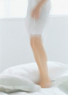 Woman standing on bed, low section, blurred