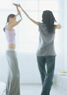 Two young women dancing, blurred