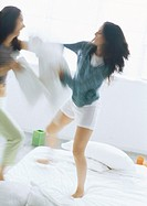 Two young women fighting with pillows, blurred motion