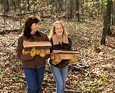 A mother and daughter carry cut wood in from the forest